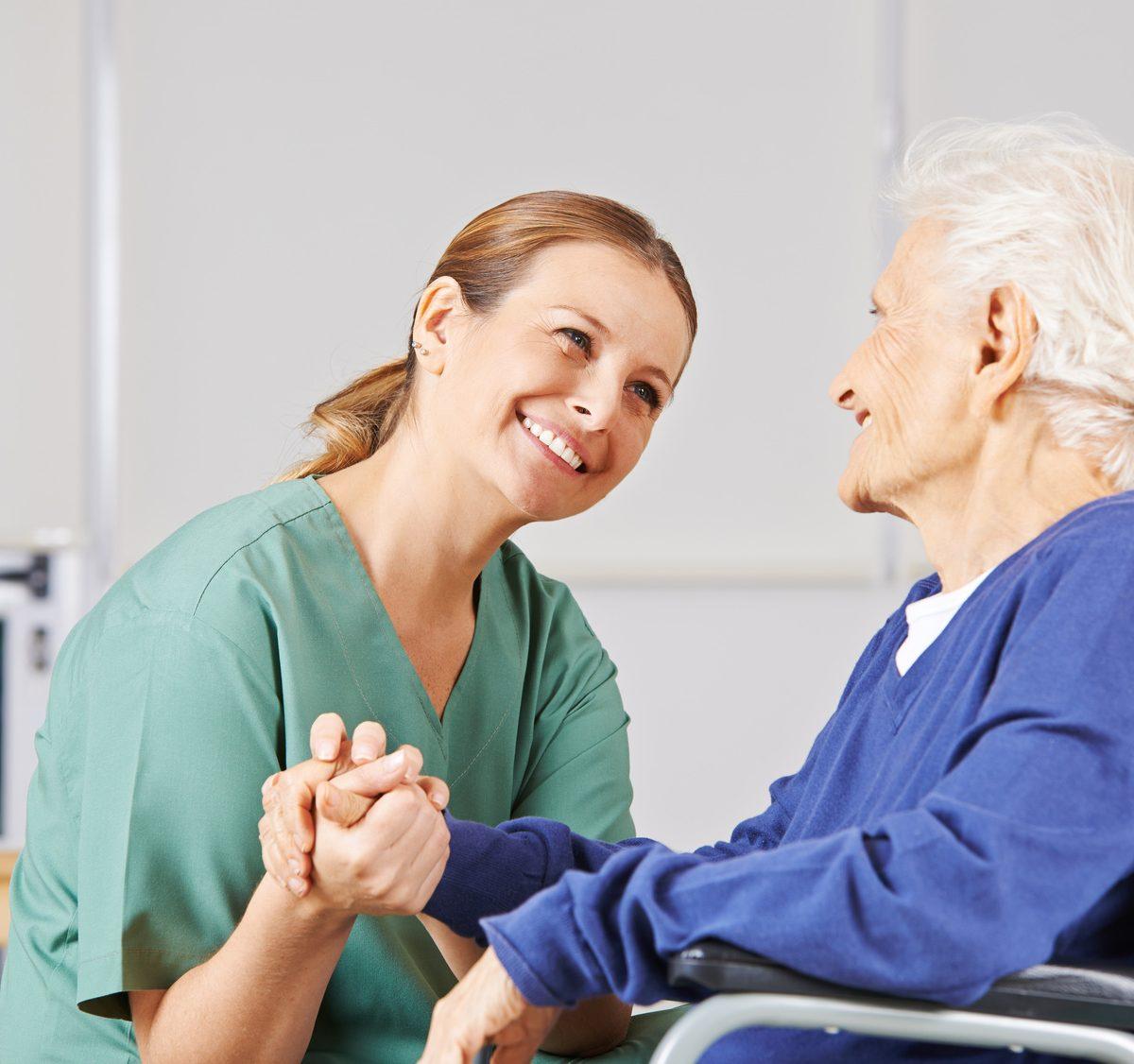 Lächelnde Krankenschwester bei der Altenpflege hält die Hand einer Seniorin